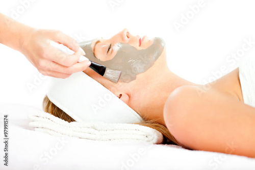 Fotografie, Obraz  Young woman having clay skin mask treatment on her face
