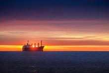 Sunrise Over The Sea With Sailing Cargo Ship