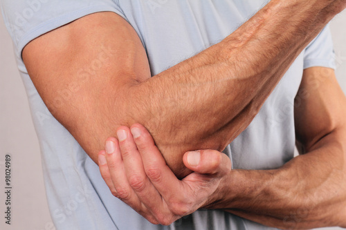 Fotografía  Man With Pain In Elbow. Pain relief concept