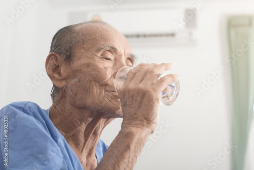 Canvas Print Old man holds and drinks glass of water