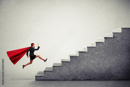 superwoman in red cloar running up stairs Wallpaper Mural