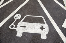 Electric Vehicle Charging Station Sign In A Parking Bay Painted On Black Asphalt