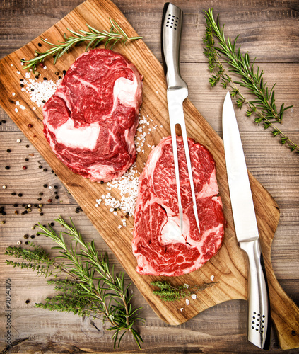 Foto op Aluminium Vlees Raw fresh meat Ribeye Steak herbs spices on wooden desk