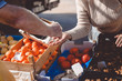 Picture of marketplace with different fruits. Buyer's and seller's hand on colorful background