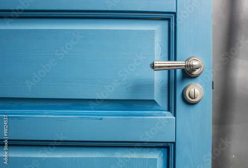 Fotografie, Obraz  open wooden door painted in blue with a beautiful a metal handle and the castle