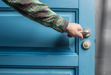 man holding on to by its metal handle in the open wooden door blue
