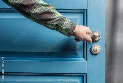 Fotografia  man holding on to by its metal handle in the open wooden door blue