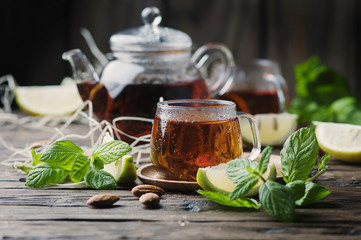 Fototapeta Hot black tea with lemon and mint on the wooden table
