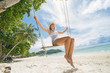 Tropical vacation. Beautiful happy woman swinging on a Tropical beach on Koh Lipe island. Thailand.