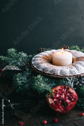 Papiers peints Dessert Traditional homemade christmas cake holiday dessert with candle in new year tree decorations frame on vintage wooden table background. Rustic style