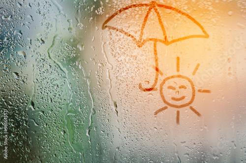 Fotografie, Obraz  draw sun holding umbella on natural water drops glass window bac
