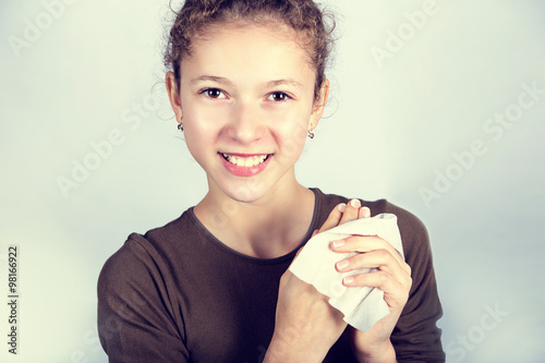 plakat Child Hygiene.Little girl cleaning her hands with a wet baby wipe isolated on a white background.