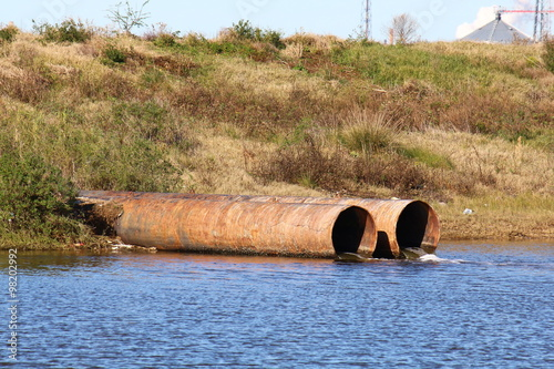 Fotografie, Obraz  Storm drain pipes emptying water into a coastal estuary viewed from side