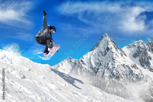 Extreme snowboarding man / Snowboarder jumping high in the air Canvas Print