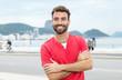 canvas print picture - Junger Mann mit Bart und rotem Shirt steht in der Stadt
