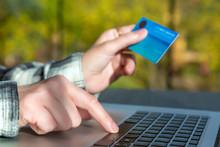 Hands Of Person Entering Credit Card Data On Laptop