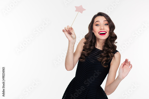 Fotografie, Obraz  Cheerful beautiful curly young woman posing with magic wand
