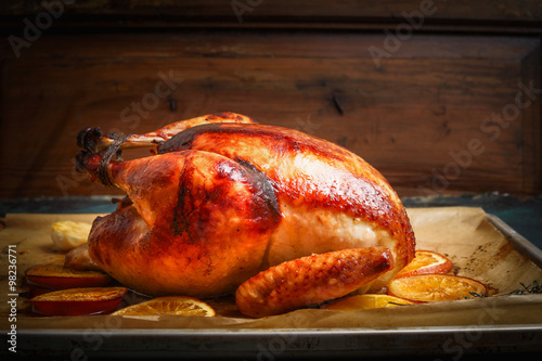 Fotografie, Obraz  Roast whole turkey or chicken over wooden background, side view