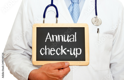 Fotografía  Annual check-up - doctor holding chalkboard with text on white background