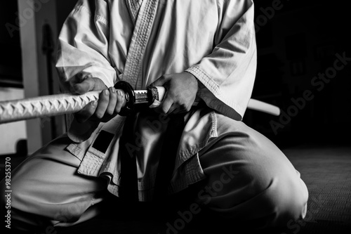 Garden Poster Martial arts Close up of young martial arts fighter with katana siting in seiza position, black and white.
