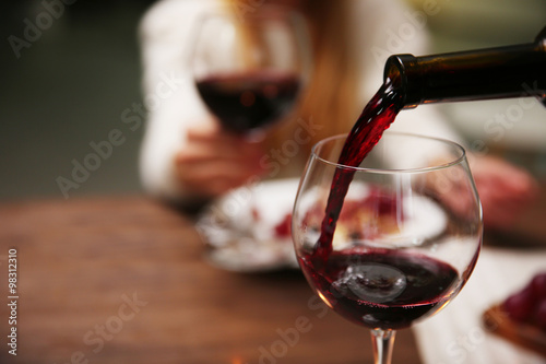 Fotografía  Pouring red wine from bottle into the wineglass