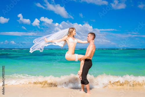 Photo  Beautiful bride in white bikini, veil and groom on the beach