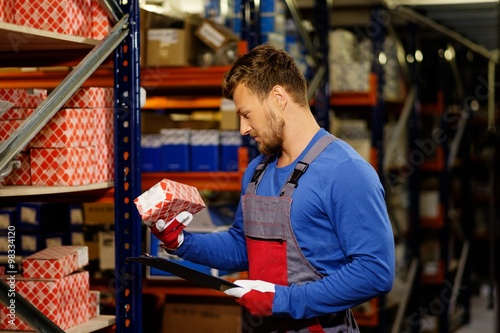 Fotografía  Worker on a automotive spare parts warehouse