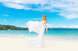 Beautiful blond bride in white wedding dress with big long train
