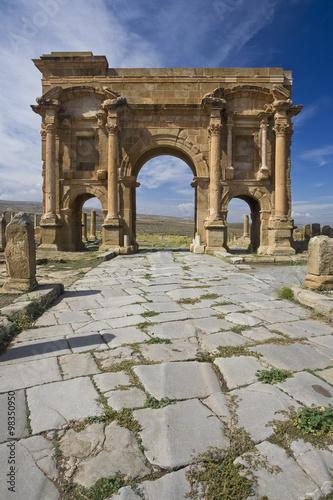 Staande foto Algerije Algeria. Timgad (ancient Thamugadi or Thamugas). Paving stones of Decumanus Maximus street and 12 m high triumphal arch, called Trajan's Arch