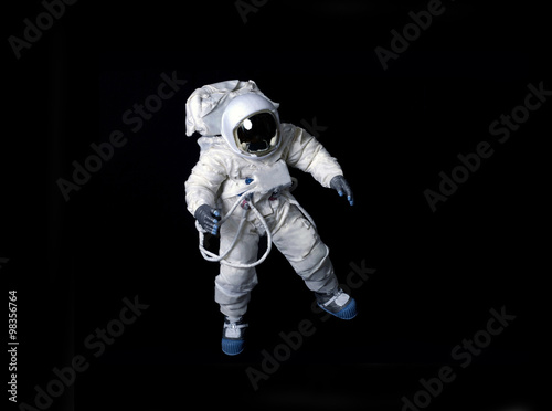 Astronaut floating against a black background.