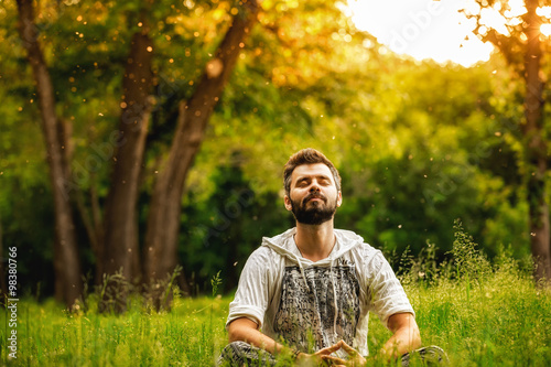 Photo  A man sitting on grass in the park and smiling with eyes closed