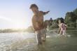 Mature woman splashing water on her husband on lake, Bavaria, Germany
