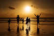 Silhouette of happy family and people running on beach