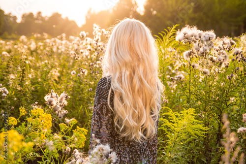 Slika na platnu Long haired blond woman turned back on sunset meadow