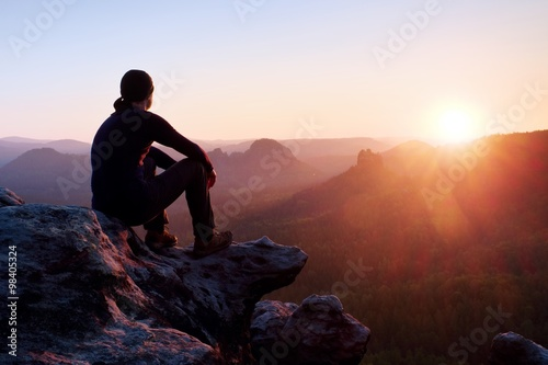 Fototapeta Tired adult hiker in black trousers, jacket and dark cap sit on cliff edge and looking to colorful mist in valley bellow obraz