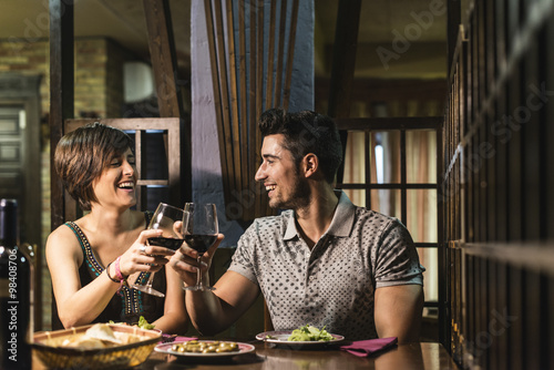 Couple smiling and drinking wine in restaurant