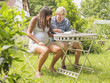 Young couple expecting baby, sitting in garden reading magazine