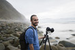 Spain, Valdovino, portrait of smiling photographer on the beach with tripod and camera