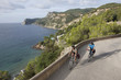 Spain, Ibiza, Mature man and mid adult woman riding bicycle
