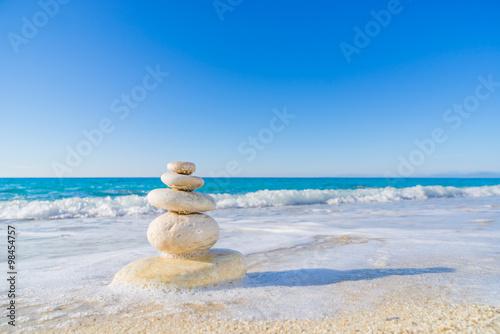 Tuinposter Stenen in het Zand Stones pyramid on sand symbolizing zen, harmony, balance. Ocean