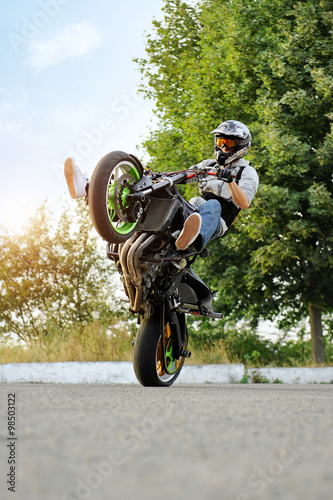 In need of extreme. Vertical soft smudged focus shot of a male biker practicing stunts on a bike