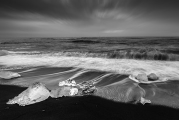 Fototapeta Czarno-Biały Ice cube with smooth wave at black sand beach Iceland black ans white tone