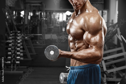 Muscular man working out in gym doing exercises with dumbbells at biceps, strong Wallpaper Mural
