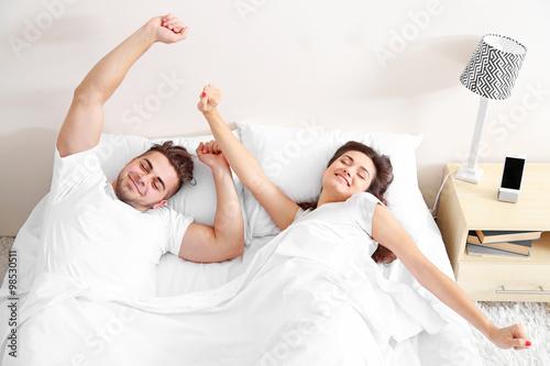 Fotografie, Obraz  Happy couple waking up with mobile alarm clock