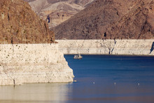 Ship Sails On Lake Mead At Hoover Dam. White Low Water Level Strip On Red Cliffs Of Lake Mead Entering Hoover Dam.