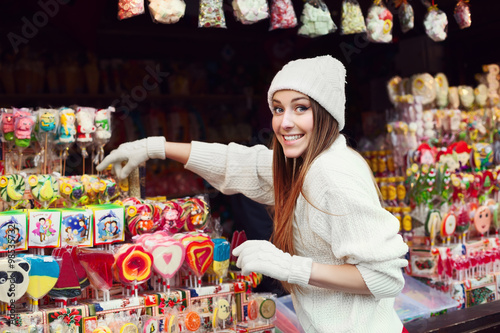 Plakát  Street portrait of smiling beautiful young woman buying candy on the festive Christmas fair