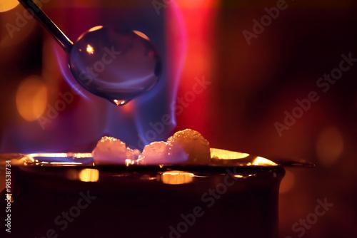 eine blaue Flamme ergießt sich über dem Zucker einer Feuerzangenbowle