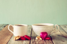 Image Of Two Red Heart Shape Chocolates And Couple Cups Of Coffee On Wooden Table. Valentine's Day Celebration Concept