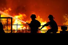 Пожарные тушат огонь на крыше дома. Силуэты пожарных на фоне пожара, огня. Двое мужчин в форме пожарных тушат огонь на крыше дома из брансбойта