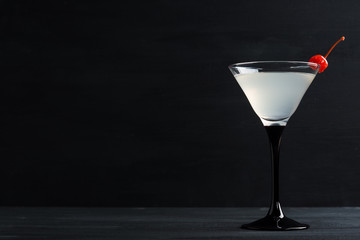 Fototapeta Cocktail in martini glass on the black wooden background